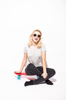 Blondie com pernas cruzadas senta-se no skate vermelho em frente a parede branca
