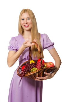 Blondie mulher segurando cesta com frutas isolado no branco