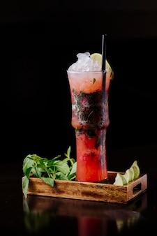 Bloody mary cocktail com molho de tomate vermelho, ervas e cubos de gelo dentro da bandeja de madeira.