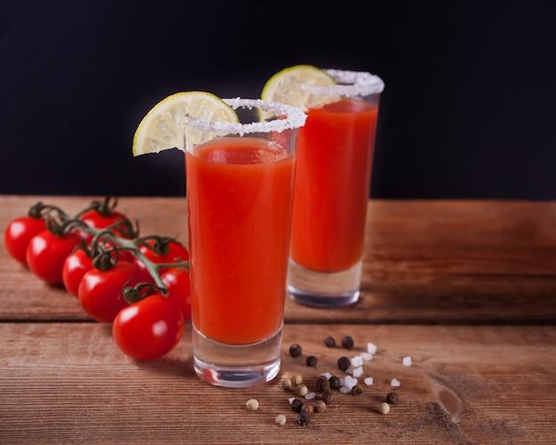 Bloody mary cocktail em copos. bebida picante do bloody mary do tomate na tabela de madeira.