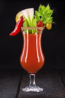 Bloody mary, uma bebida vermelha à base de vodka, suco de tomate, suco de limão, aipo, ervilhas, molho e pimenta, em uma superfície preta