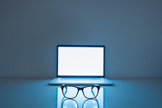 Bloqueadores de luz azuis e laptop em fundo escuro