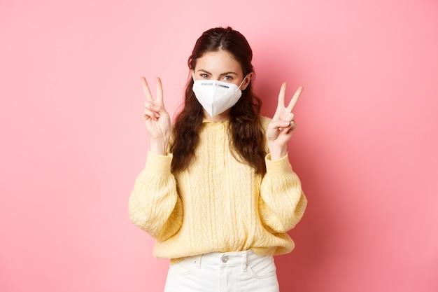 Bloqueio de covid e conceito de pandemia linda garota glamourosa usa respirador médico para sair durante a quarentena. mostra a paz vsign fica contra a parede rosa