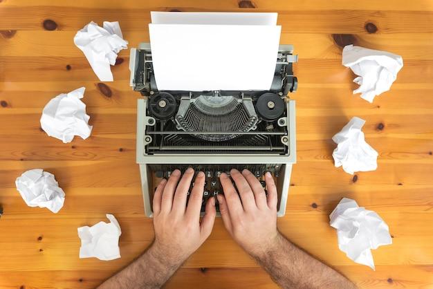 Bloqueio de escritor. máquina de escrever e papel amassado na mesa de trabalho. conceito de processo criativo