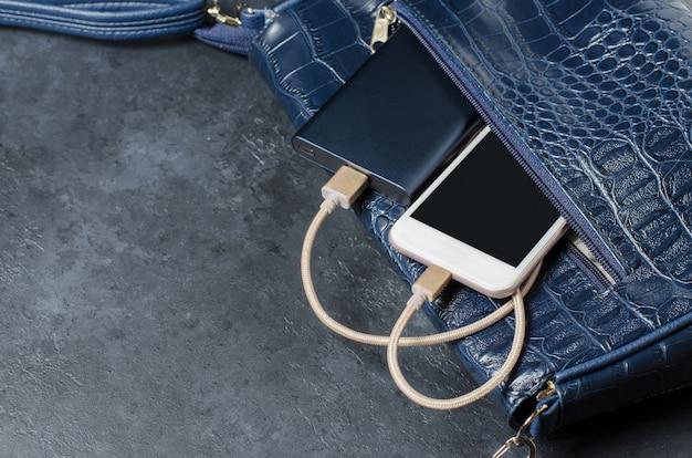 Blue power bank e telefone na bolsa feminina. fundo de concreto cinza escuro. copie o espaço