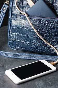 Blue power bank e telefone na bolsa feminina. fundo de concreto cinza escuro. foto vertical