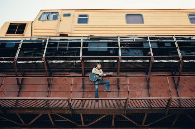 Bluesman com violão na ponte da estrada de ferro. legal cara toca guitarra perto de trem em execução. desempenho vistoso do músico de blues.