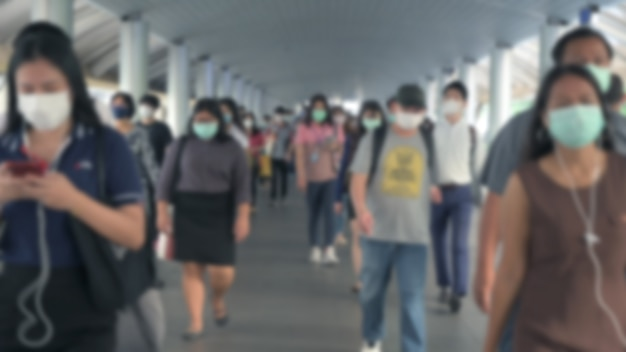 Blured desfocado. a multidão está usando máscaras protetoras para impedir o vírus coronavirus, covid 19 durante o surto de vírus e a hora do rush da crise da poluição do ar pm2.5 em bangkok, tailândia.