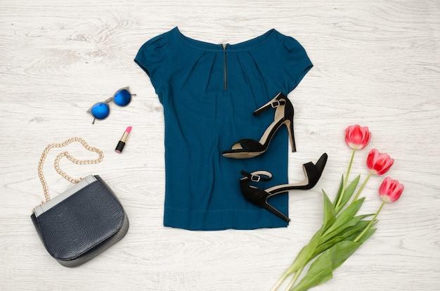 Blusa azul, bolsa, óculos redondos, batom, sapatos pretos e tulipas cor de rosa