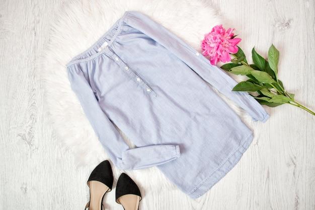 Blusa azul, sapatos pretos e peônia rosa. conceito elegante