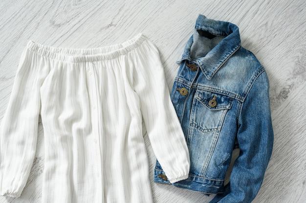 Blusa branca e jaqueta jeans em madeira. conceito elegante