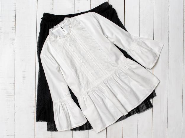 Blusa branca na saia preta.
