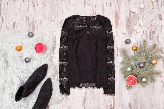 Blusa de renda preta, sapatos e ramo de abeto decorado em fundo de madeira.