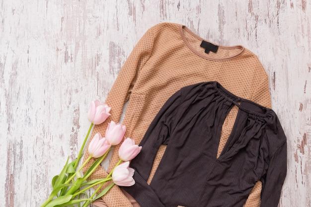 Blusa dourada e preta, tulipas cor de rosa em um fundo de madeira. conceito elegante