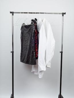 Blusa feminina preta com lantejoulas vermelhas, camisas brancas masculinas penduradas em um cabide de ferro branco