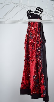 Blusa feminina preta com lantejoulas vermelhas penduradas em um cabide de ferro branco