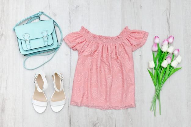 Blusa rosa, sapatos brancos, bolsa e um buquê de tulipas.