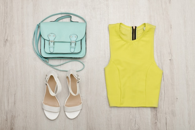 Blusa verde clara, sapatos brancos e bolsa. superfície de madeira.