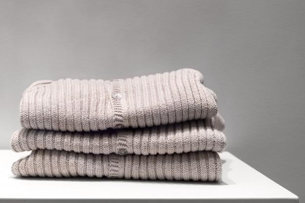 Blusas bege feitas de tecidos naturais são dobradas na mesa.