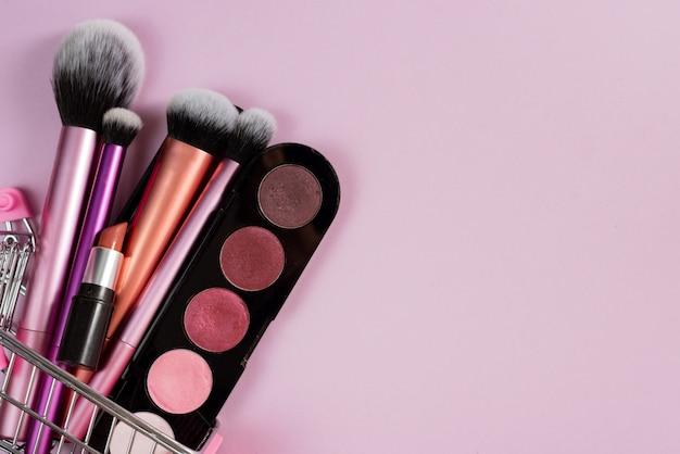 Blush de sombra para os olhos, batom e vários pincéis de maquiagem em um carrinho rosa do comprador. o conceito de compras on-line de cosméticos decorativos, descontos nas lojas