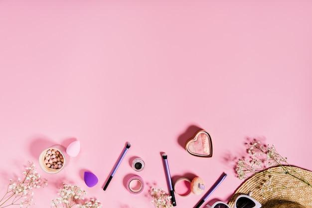 Blush, pincéis de maquiagem lilás e chapéu de palha estão localizados no rosa isolado.