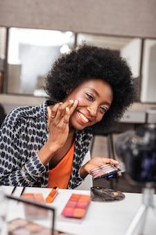 Blusher. mulher bonita de pele escura com maquiagem brilhante sorrindo positivamente enquanto aplica blush nas bochechas