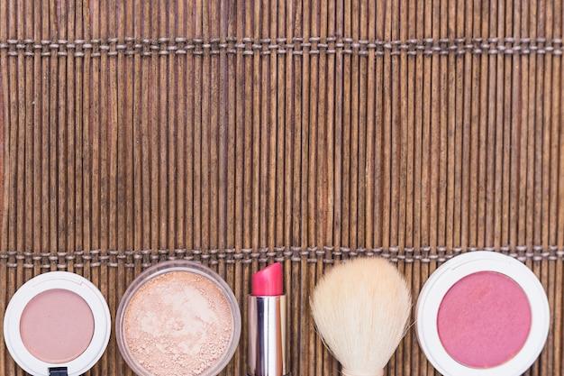 Blusher; pó compacto; batom e esponja e pincel de maquiagem em placemat