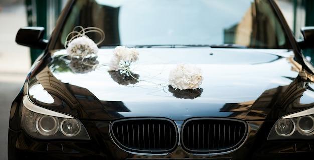 Bmw preto decorado com buquês de casamento branco