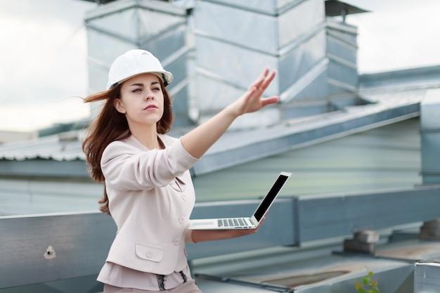 Boa aparência empresária em terno bege, calça marrom e capacete sentar no telhado e segure laptop