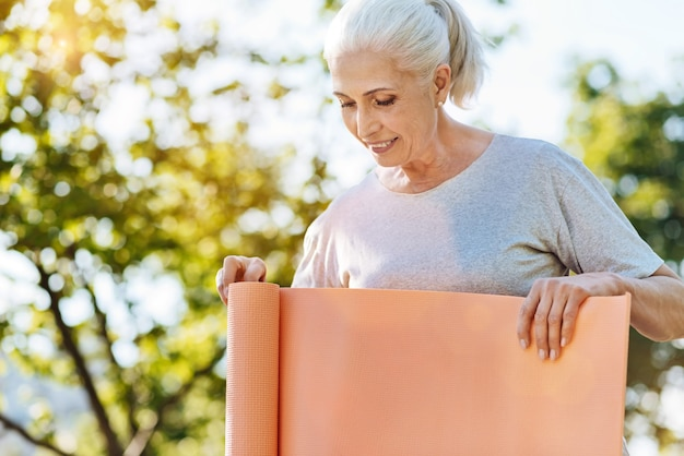 Boa atividade. mulher sênior feliz e alegre desenrolando tapete de ioga