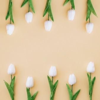 Boa composição com tulipas em fundo amarelo com espaço no meio