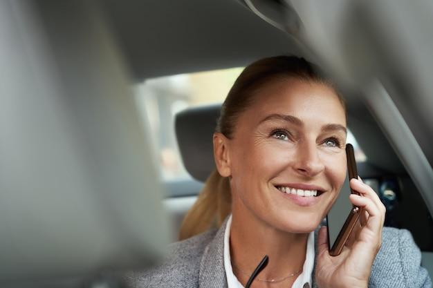 Boa conversa, retrato de uma mulher de negócios atraente bem-sucedida falando ao telefone celular e sorrindo