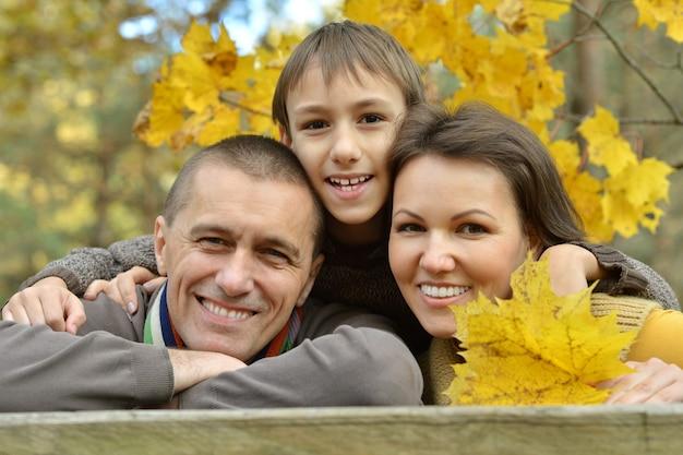 Boa família feliz dando um passeio no parque de outono
