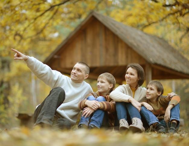 Boa família feliz relaxando no parque de outono