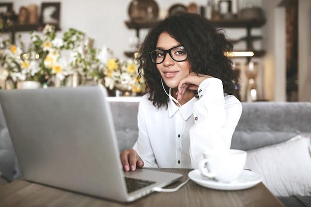 Boa garota afro-americana de óculos, sentado no restaurante com o laptop e a xícara de café. jovem senhora com cabelo escuro e encaracolado trabalhando em um laptop com fones de ouvido