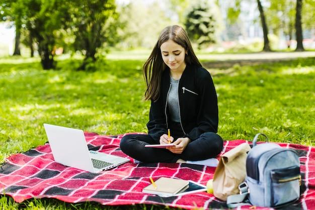 Boa garota escrevendo e estudando no parque