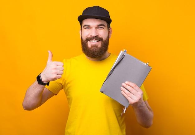 Boa gestão, gerencie seu tempo com planejador, homem mostrando o polegar para cima e segurando a agenda