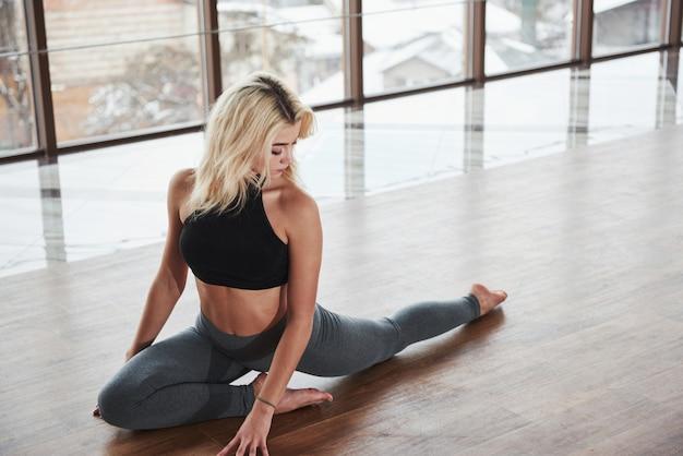 Boa iluminação. garota loira atraente com bom corpo, fazendo exercícios de aquecimento para as pernas