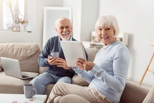 Boa manhã. casal de idosos alegres, sentado na sala de estar, lendo postagens nas redes sociais e rindo enquanto o homem bebe café