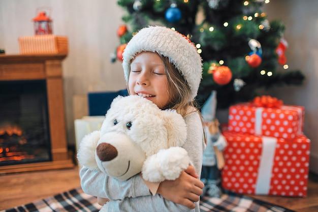 Boa menina pequena abraçando seu brinquedo e mantendo os olhos fechados.