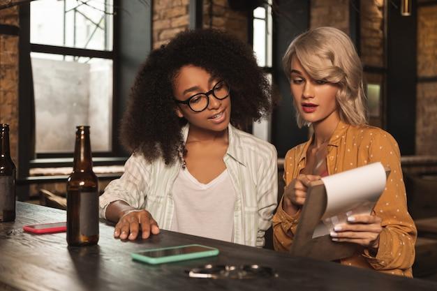 Boa oferta. moças agradáveis sentadas no balcão do bar do pub e verificando o cardápio, decidindo sobre o pedido