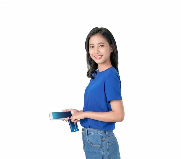 Boa pele asiática da mulher que guarda o smartphone e o cartão de crédito que compram em linha com sorriso brilhante.