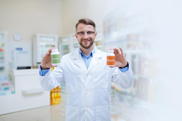 Boa qualidade. químico jovem e bonito com um sorriso no rosto enquanto demonstra probióticos