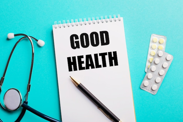 Boa saúde escrita em um bloco de notas branco perto de um estetoscópio, canetas e comprimidos em um azul claro