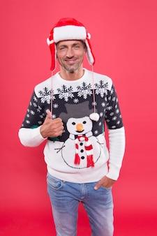 Boa sorte. homem bonito comemorar fundo vermelho de férias de inverno. cara usa um suéter de inverno. feliz natal e feliz ano novo. muitas felicidades. férias de inverno. homem maduro com chapéu, rosto sorridente eriçado.