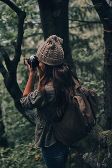 Boa tentativa. jovem mulher moderna com mochila, fotografando a natureza durante uma caminhada na floresta