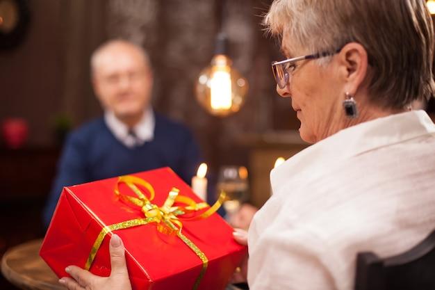 Boa velhinha olha o presente que o marido lhe deu enquanto jantava. casal na casa dos sessenta. casal velho romântico. casal jantando em um restaurante.