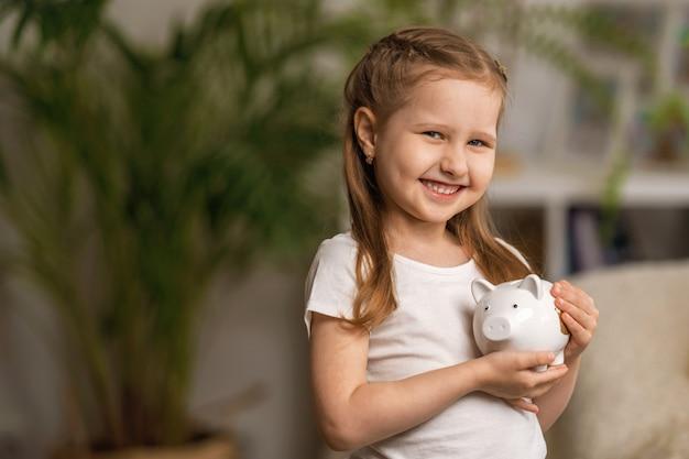 Boas economias. uma menina bonita com um cofrinho em casa