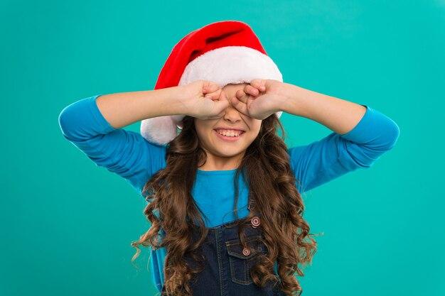 Boas férias de inverno. menina pequena. presente para o natal. infância. festa de ano novo. criança de papai noel. compras de natal. menina com chapéu de papai noel. o natal está aqui. capturando um momento feliz.
