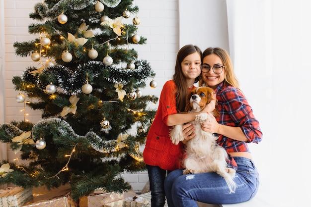 Boas férias de inverno! mulher morena positiva abraça a pose de menina com presentes no chão da sala, cachorro perto, divirta-se perto da árvore de natal.
